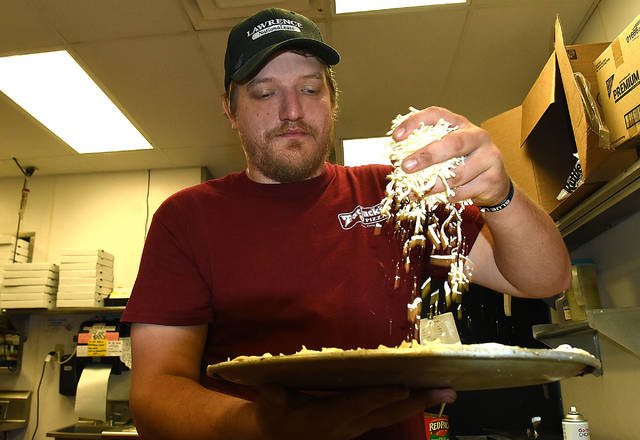 Brandon Goedde of Fat Jacks Pizza, makes a cheese pizza during the lunchtime rush at the North West Street pizzeria.