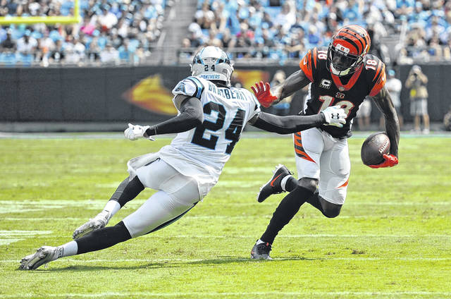 Cincinnati Bengals' A.J. Green (18) runs after a catches Carolina Panthers' James Bradberry (24) defends during the first half of an NFL football game in Charlotte, N.C., Sunday.