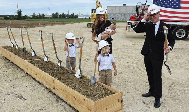 Nick Kennedy, far right, puts on a hardhat to break ground for his new $4 million, 55,00 sq., ft. Flex Arm facility in Wapakoneta with his wife, Ashley and three children, Weston, 6, Warren, 4, and Vanna, three-months. Craig J. Orosz | The Lima News