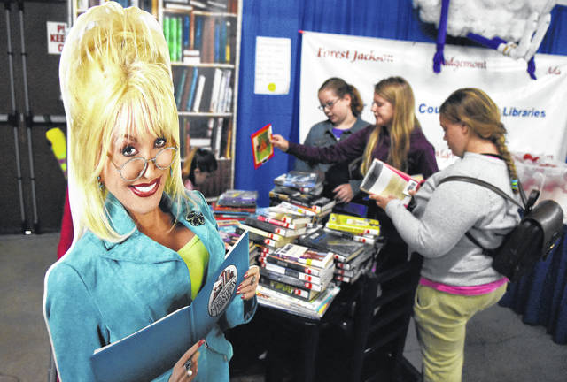 FILE - A cut-out of singer Dolly Parton smiles as Lucy Whitmer, 10, left, Kenzie Kugel, 10, and Logan Smith, 13, select free library books from Hardin County Public Library free book display at the 2017 Hardin County Fair.