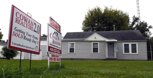 For sale signs are on display in the front yard of a home in Elida.