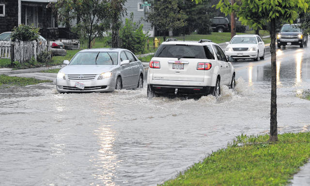 Cars drive in flooded water on Kibby Street Thursday evening. The weekend is expected to be a wet one.