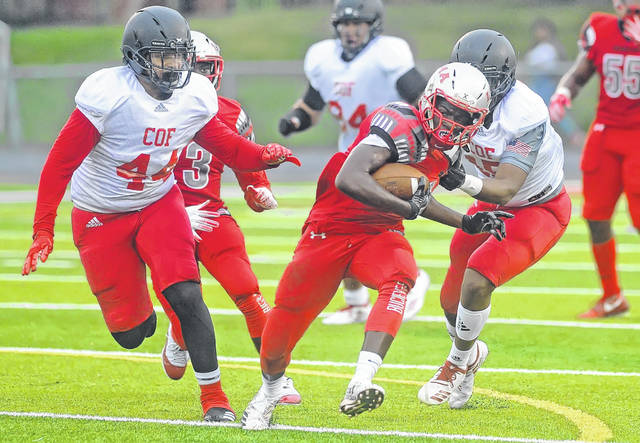 Lima Senior's Mizhir McMillian rushes for yards against COF Academy's Jordell Smith, left, and Zyaire Sejour during Friday night's game at Spartan Stadium. McMillen rushed for 104 yards on 16 carries. See more game photos at LimaScores.com.