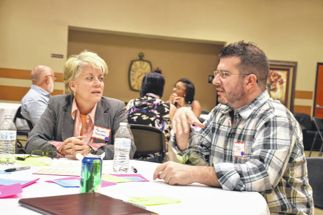 Marianne Bradshaw, left, speaks with Jay Doute during a session for Your Voice Ohio held Thursday night at the UNOH Event Center in Lima.