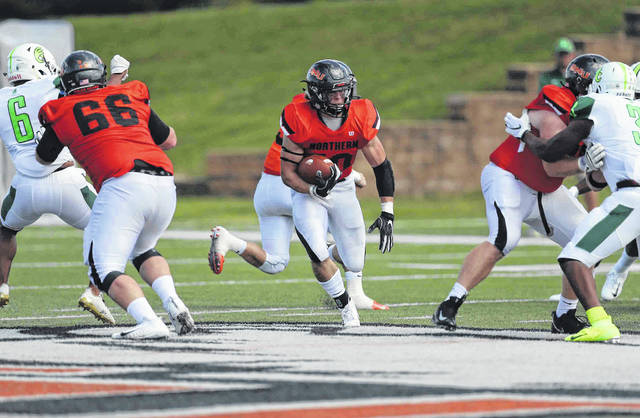 Ohio Northern's Kyle Gonterman (66) and Sam Shook (right) provide running room for Brock Martin during Saturday's game against Wilmington at Dial Robinson Stadium in Ada.