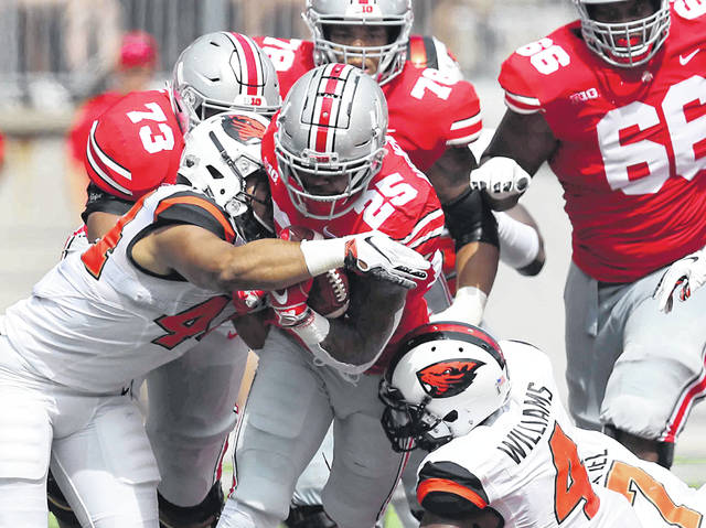 Ohio State's Mike Weber fights for yards against Oregon State's Isaiah Tufaga, left, and Dwayne Williams during Saturday's game at Ohio Stadium in Columbus.