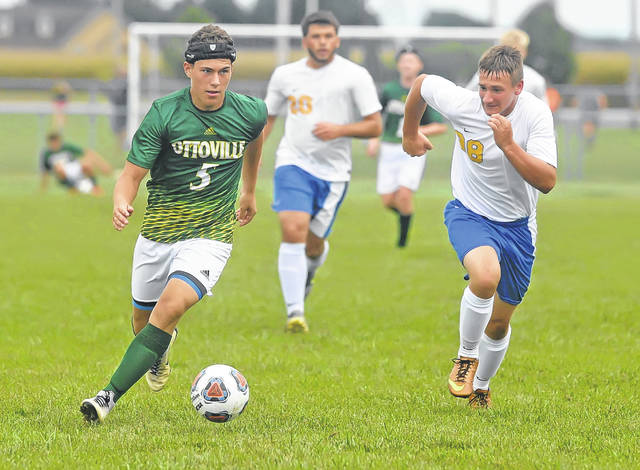 Ottoville's Dalton Davis dribbles past Continental's Luke Recker during Monday's match at Ottoville.  Richard Parrish | The Lima News