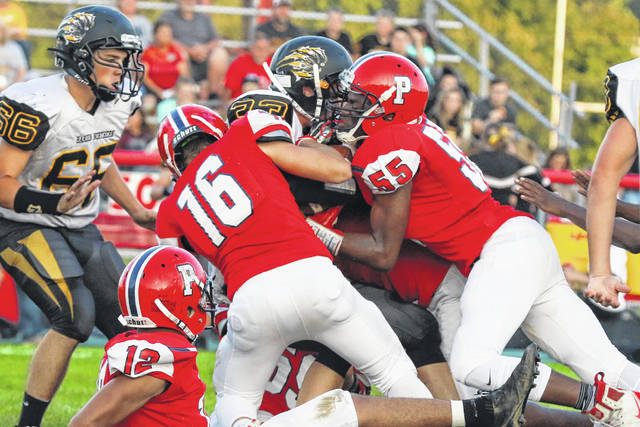 Perry's Rashad Davis (55) and Brayden Owens (16) halt the progress of Hardin Northern's Franklin McCoy during Friday night's game at Perry. The Perry defense gave up just 13 points, while the offense rolled up 424 yards and 75 points in a lopsided victory.