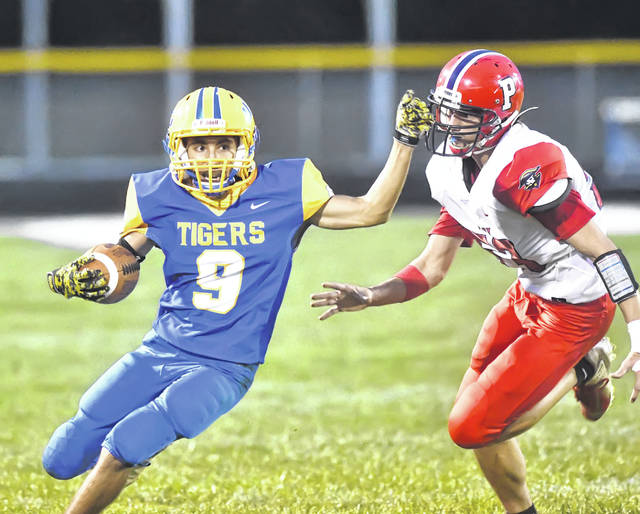 Perry's Timothy Hendley chases Waynesfield-Goshen's Wesley Eller during Friday night's game at Waynesfield.