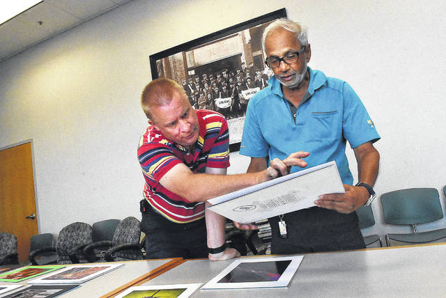 Michael J. Ayers, president of The Ayers Inc. Photography. left, and Dr. Randy Bansal judge the best of show during the 2018 Lima News Amateur Photo competition.