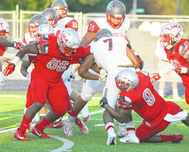 Lima Senior's Jordan McClendon (58) and Caymen Durr join forces in tackling Toledo Central Catholic's Jonsell Norrils (7) during Friday night's game at Spartan Stadium.