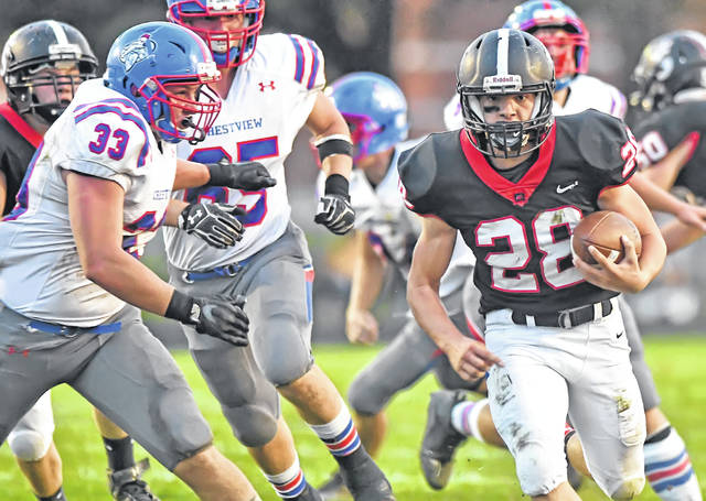 Spencerville's Joel Lutz gets away from Crestview defenders during Friday night's Northwest Conference game at Memorial Field in Spencerville.