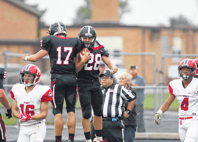 Spencerville's Jackson Goecke (17) and Joel Lotz celebrate after Lotz's touchdown during Friday night's game against Perry at Spencerville.