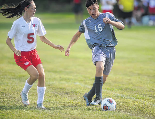 New Knoxville's Jacklyn Leffel defends Temple Christian's Joshua Engle during Tuesday night's match at Temple Christian. See more match photos at LimaScores.com.