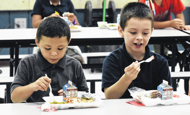 Xavier Whitted, 7, and Aiden Mendenhall, 8, kick off the Crave the FAV by eating fresh fruit during lunch at Freedom Elementary School on Wednesday. Interns, who are studying to sit for the Registered Dietitian Nutritionist exam, will conduct research on whether the educational component makes an impact on students choosing to eat more fruits and vegetables.