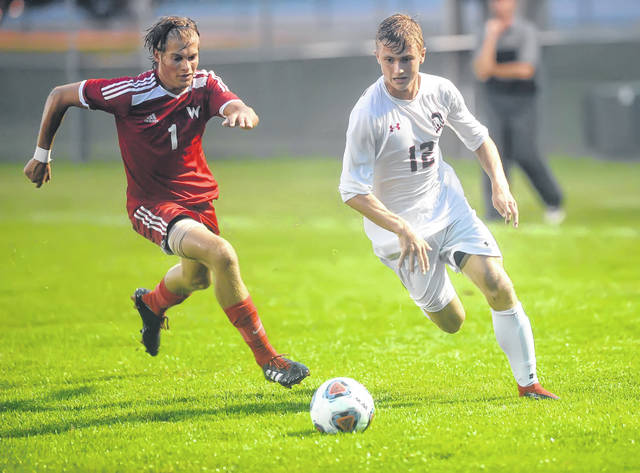 Wapakoneta's Tristan Gesler (1) chases Shawnee's Jacob Miller during Thursday night's match at Ryan Field in Wapakoneta. See more match photos at LimaScores.com.