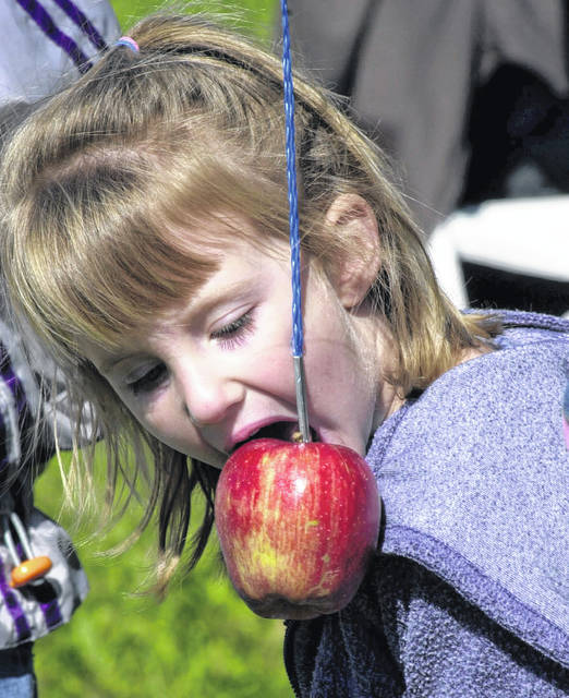Competing in the apple eating contest, Abby Pennington tries to take a bite from her apple on a string at the Apple Festival at the Allen County Farm Park.