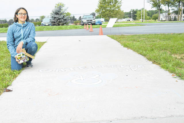 Grace Wood, 14, a Bath High School freshmen, is a member of the new Gatekeepers suicide prevention club at Bath High School. Wood created sidewalk art for the Gatekeepers 5K race held at Bath schools Saturday which was signed by members of the new club, including Gatekeepers president Emily Vandemark.