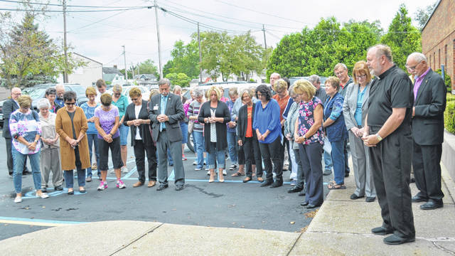 The Rev. Matt Jozefiak (right) leads a group of people, including the Putnam County commissioners, volunteers for Heartbeat of Lima Inc. and Lima and Putnam County residents in prayer Tuesday during the grand opening of a new Ottawa branch of Heartbeat of Lima at 1225 E. Third St.