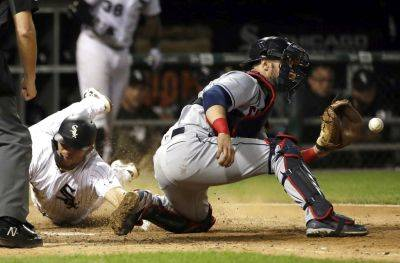 The White Sox's Yolmer Sanchez scores as Cleveland's Yan Gomes catches the ball during the ninth inning of Tuesday night's game in Chicago. (AP photo)