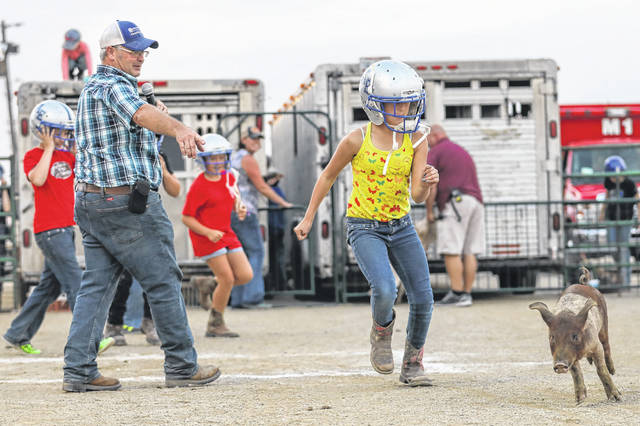 Vanessa Cross, 11, of Bluffton chases pigs during the livestock scramble held at the grandstands of the Allen County Fair. Find past coverage and photos from the fair at LimaOhio.com/tag/fair.