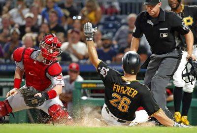 The Pirates' Adam Frazier slides safely into home before Cincinnati's Tucker Barnhart can tag him on third inning single by Gregory Polanco during Tuesday night's game in Pittsburgh. AP photo