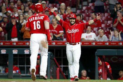 The Reds' Eugenio Suarez waits to greet teammate Tucker Barnhart (16) at home plate after Barnhart his a home run during the ninth inning of Friday night's game in Cincinnati. (AP photo)
