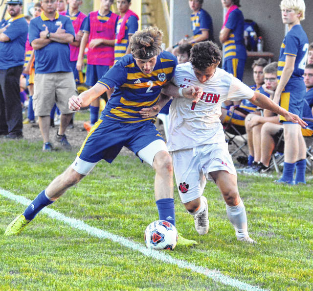 Allowing the ball to roll out of bounds for a throw-in, St. Marys Roughrider defender Max Mielke shields the ball from Kenton Wildcat Nick Anderson in a Western Buckeye League match at St. Marys Monday.