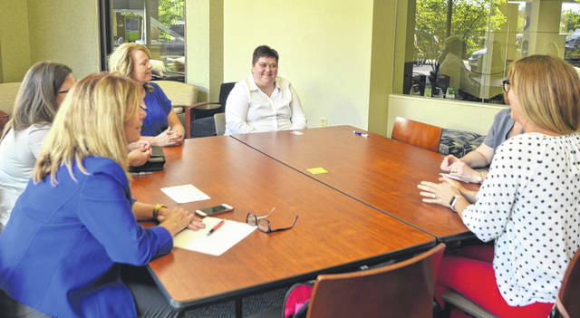 Members of the Patient Treatment Intervention Team — Renee Goodwin, Susan Hawk, Danielle Schimmoeller, Patty Blevins, and Katie Thompson — meet with patient Serena Coulter, face not shown, to discuss her progress with coping with her mental illnesses at Mercy Health-St. Rita's Medical Center.