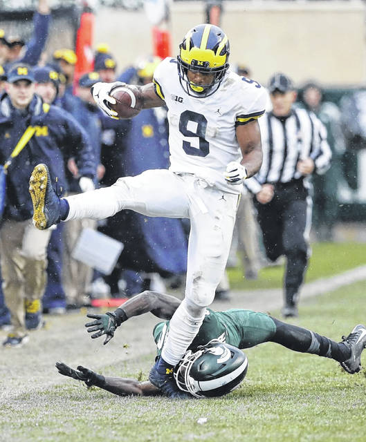 Michigan's Donovan Peoples-Jones (9) jumps over Michigan State's Tre Person (24) enroute to a 79-yard touchdown run during Saturday's game in East Lansing, Mich.