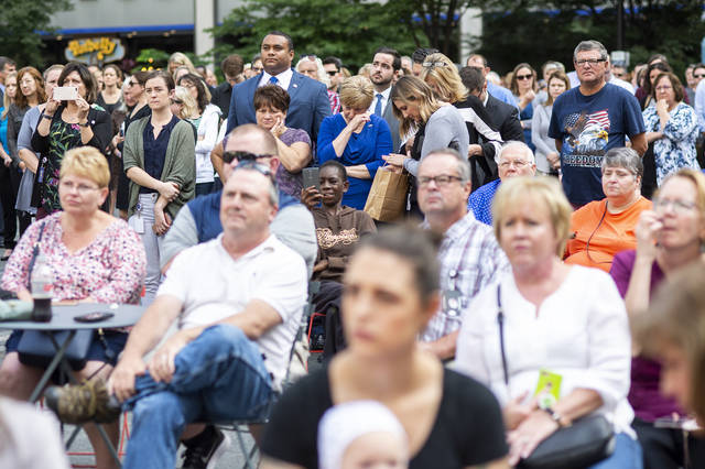 Hundreds of people gathered at Cincinnati's downtown Fountain Square on Monday, Oct. 1, 2018, for a ceremony honoring valor and distinguished service shown by police officers and citizens who helped save lives when a man fatally shot three people and injured two in a bank lobby last month. (AP Photo/Angie Wang)