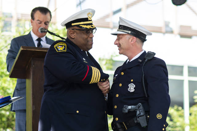 Police Chief Eliot Isaac, left, shakes hands with Specialist Gregory Toyeas before awarding him a Medal of Valor in Cincinnati on Monday, Oct. 1, 2018. The ceremony honored valor and distinguished service shown by police officers and citizens who helped save lives when a man fatally shot three people and injured two in a bank lobby last month. (AP Photo/Angie Wang)