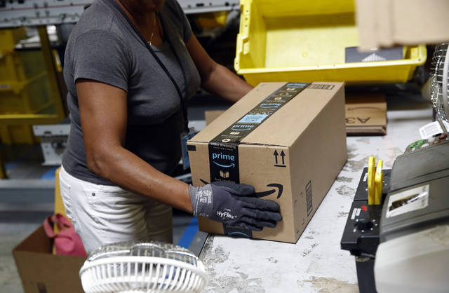 FILE- In this Aug. 3, 2017, file photo, Myrtice Harris applies tape to a package before shipment at an Amazon fulfillment center in Baltimore. Amazon is boosting its minimum wage for all U.S. workers to $15 per hour starting next month. The company said Tuesday, Oct. 2, 2018, that the wage hike will benefit more than 350,000 workers, which includes full-time, part-time, temporary and seasonal positions. (AP Photo/Patrick Semansky, File)