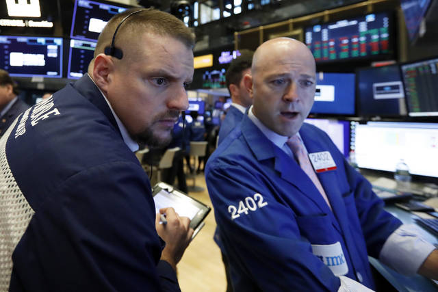 FILE- In this Tuesday, Oct. 2, 2018, file photo trader Michael Milano, left, and specialist Jay Woods work on the floor of the New York Stock Exchange. The U.S. stock market opens at 9:30 a.m. EDT on Wednesday, Oct. 3. (AP Photo/Richard Drew, File)