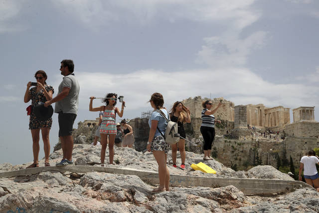 FILE - In this Monday, July 23, 2018 file photo, tourists take photographs as the ancient Acropolis hill is seen in the background in Athens. A Greek union representing staff at the country's ancient sites and state-run museums has called a 24-hour strike for Oct. 11. The protest is likely to close the ancient Acropolis in Athens that day along with multiple sites around Greece that are popular with tourists. (AP Photo/Thanassis Stavrakis, File)