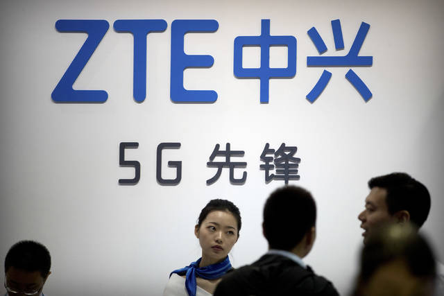 FILE - In this Sept. 26, 2018, file photo, staff members stand at a display for Chinese technology firm ZTE at the PT Expo in Beijing. Chinese tech stocks Lenovo Group and ZTE Corp. have tumbled in Hong Kong following a news report Chinese spies might have used chips supplied by another company to hack into U.S. computer systems. (AP Photo/Mark Schiefelbein, File)