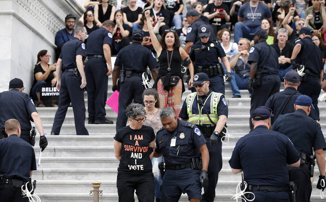 Activists are arrested by Capitol Hill Police officers after occupying the steps on the East Front of the U.S. Capitol as they protest the confirmation vote of Supreme Court nominee Brett Kavanaugh on Capitol Hill, Saturday, Oct. 6, 2018 in Washington. (AP Photo/Alex Brandon)