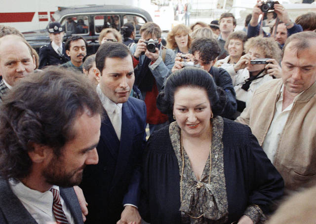 FILE - In this Monday, Oct. 10, 1988 file photo, rock star Freddie Mercury, center left, lead singer of the pop group Queen, arrives with opera star Montserrat Caballe at the Royal Albert Hall in London to publicize their hit song 'Barcelona.' Spanish opera diva Montserrat Caballe, renowned for her bel canto technique and her interpretations of the roles of Rossini, Bellini and Donizetti, has died. She was 85. Hospital Sant Pau press officer Abraham del Moral confirmed her passing away early on Saturday Oct. 6, 2018. (AP Photo/Martin Cleaver, File)
