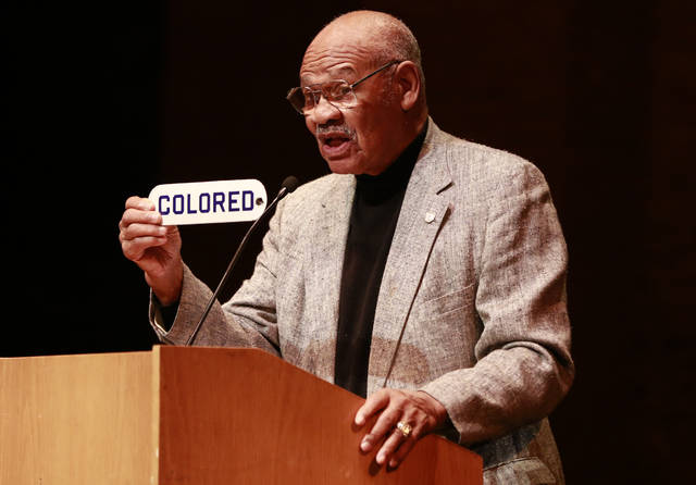 "FILE - In this Dec. 6, 2012, file photo, Indiana University alumnus and former NFL player George Taliaferro holds the ""COLORED"" sign he took from the Princess Theater during the 1940s, when all the Bloomington theaters were segregated, in Bloomington, Ind. He spoke at a celebration of the 90-year-old Indiana Theater. Taliaferro, a standout running back for Indiana who became the first black player to be drafted by an NFL team when George Halas and the Chicago Bears took him in the 13th round of the NFL draft, has died. He was 91. Senior associate athletic director Jeremy Gray said Tuesday, Oct. 9, 2018, the Hoosiers had spoken with Taliaferro's family about his death in Mason, Ohio. (AP Photo/Bloomington Herald-Times, Jeremy Hogan)/The Herald-Times via AP)"