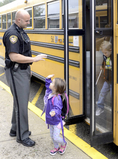 This April 2018 photo shows Stark County Sheriff's Department Deputy Chad Smith giving a high five to Ainsley Marcum at Middlebranch Elementary School in Canton, Ohio. As schools around the country grapple with how to fund security improvements and mental health services, some Ohio districts are hoping to raise millions of dollars by banding together to put the issue before voters this November, while others are making a ballot push independently. (The Canton Repository via AP)