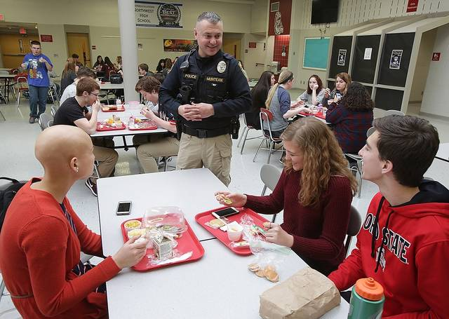 This Wednesday, Feb .14, 2018 photo shows Northwest School District School Resource Officer Dennis Muntean talking with students, Olivia Wyles, left to right, Cora Jandecka, and Ian Yoder during their lunch period at Northwest High School on Canal Fulton, Ohio. The district was among 16 that jointly proposed a levy earlier this year under a new Ohio law that enables districts to band together to seek funding specifically for school security and mental health services.(Kevin Whitlock/IndeOnline.com via AP)