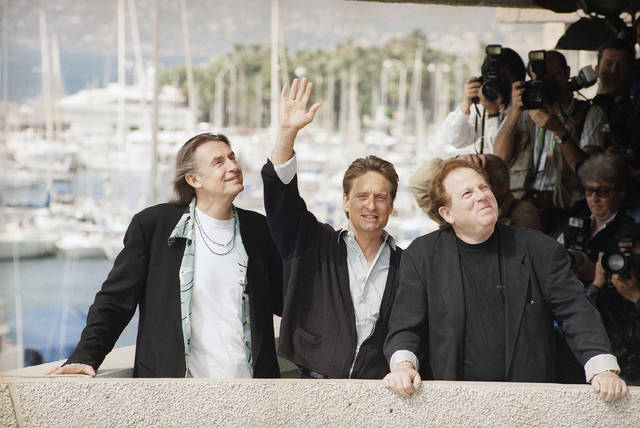 "FILE - In this May 22, 1993 file photo, American actor Michael Douglas, center, surrounded by American film director Joel Schumacher, left, and producer Arnold Kopelson, right, pose together for photographers before the press conference of their film ""Falling Down"" in competition screening at the 46th International Film Festival in Cannes, France. Kopelson, a versatile film producer whose credits ranged from the raunchy teen smash ""Porky's"" to the Holocaust drama ""Triumph of the Spirit"" to the Oscar-winning ""Platoon,"" died Monday, Oct. 8, 2018, at age 83. Family spokesman Jeff Sanderson told The Associated Press that Kopelson died of natural causes at his home in Beverly Hills, Calif. (AP Photo/Gilbert Tourte, File)"