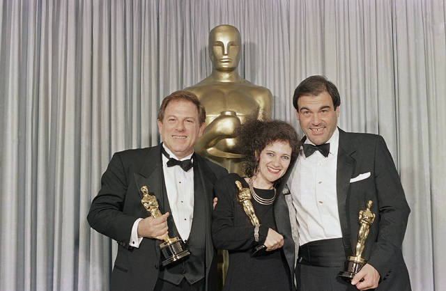 "FILE - In this Monday, March 31, 1987 file photo, Claire Simpson, center, is flanked by Arnold Kopelson, left, and Oliver Stone as the threesome meets backstage at the Dorothy Chandler Pavilion in Los Angeles after receiving Oscars, for best editing (Simpson), best direction (Stone) and best picture (Kopelson) for the film, ""Platoon."" Kopelson, a versatile film producer whose credits ranged from the raunchy teen smash ""Porky's"" to the Holocaust drama ""Triumph of the Spirit"" to the Oscar-winning ""Platoon,"" died Monday, Oct. 8, 2018, at age 83. Family spokesman Jeff Sanderson told The Associated Press that Kopelson died of natural causes at his home in Beverly Hills, Calif. (AP Photo/Lennox McLendon, File)"