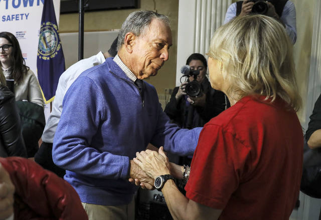 Former New York Mayor Michael Bloomberg talks to a woman who lost her daughter to gun violence after speaking at a rally at City Hall in Nashua, N.H. Saturday, Oct. 13, 2018. (AP Photo/ Cheryl Senter)