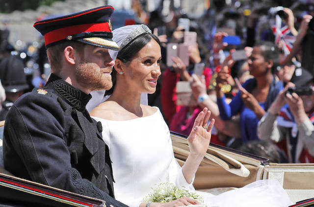 Britain's Prince Harry and his bride Meghan Markle, ride in a carriage after their wedding ceremony May 19 at St. George's Chapel in Windsor Castle in Windsor, near London. Kensington Palace announced Monday that Prince Harry and the Duchess of Sussex are expecting a child in spring 2019.