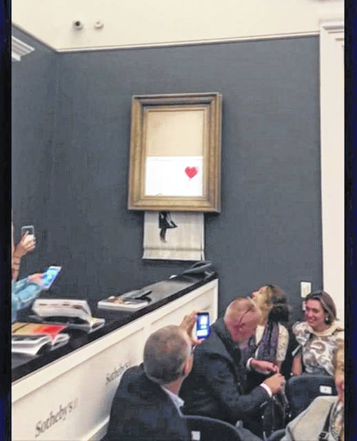 "In this file image taken from video on Oct. 5, people watch as the spray-painted canvas ""Girl with Balloon"" by artist Banksy is shredded at Sotheby's in London. Sotheby's says the winning bidder for a Banksy painting that self-destructed during an auction last week has decided to go through with the purchase. Just after the hammer came down, the bottom half of the work passed through a shredder concealed in the frame."