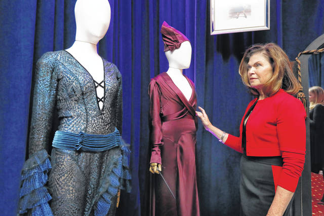 "Colleen Atwood appears with two of her designs from ""Fantastic Beasts: The Crimes of Grindelwald"" during a preview of the Neiman Marcus Christmas Book. The Oscar-winning costume designer will design a custom piece and treat two for the day to lunch, swag and a possible film set tour of whatever project she might be working on at the time for $300,000."