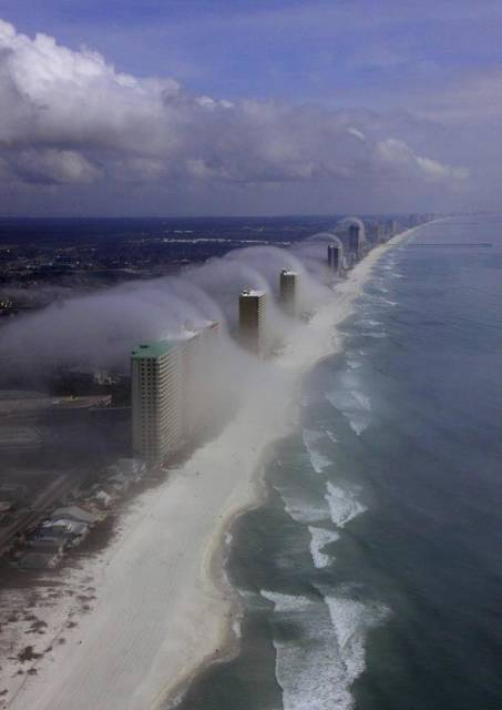 In this Feb. 5, 2012 photo provided by JR Hott, clouds roll over Panama City Beach, Fla., high-rise buildings. The photo was misrepresented by Facebook users to suggest it was taken during Hurricane Michael. (JR Hott via AP)