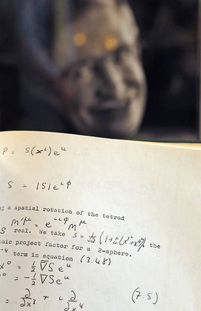A Book, written and corrected with handwritten annotation by Stephen Hawking is one of the personal and academic possessions of Stephen Hawking, photo behind, on display at the auction house Christies in London, Friday, Oct. 19, 2018.  The online auction announced Monday Oct. 22, 2018, by auctioneer Christie's features 22 items from Hawking, including his doctoral thesis on the origins of the universe, with the sale scheduled for 31 October and 8 November. (AP Photo/Frank Augstein)