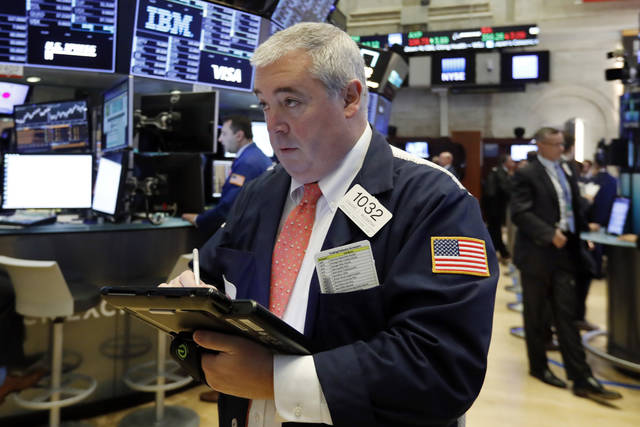 Trader Edward McCarthy work on the floor of the New York Stock Exchange, Monday, Oct. 22, 2018. U.S. stocks veered broadly lower in early trading Monday as losses in health care companies and banks outweighed gains elsewhere. (AP Photo/Richard Drew)